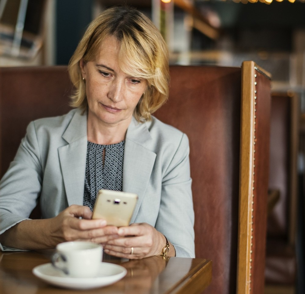 Business woman looking contemplatively at phone